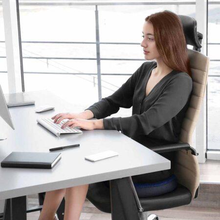 Dieses Bild veranschaulicht eine junge Frau an einem Schreibtisch sitzend auf casimum® Büro Sitzkissen