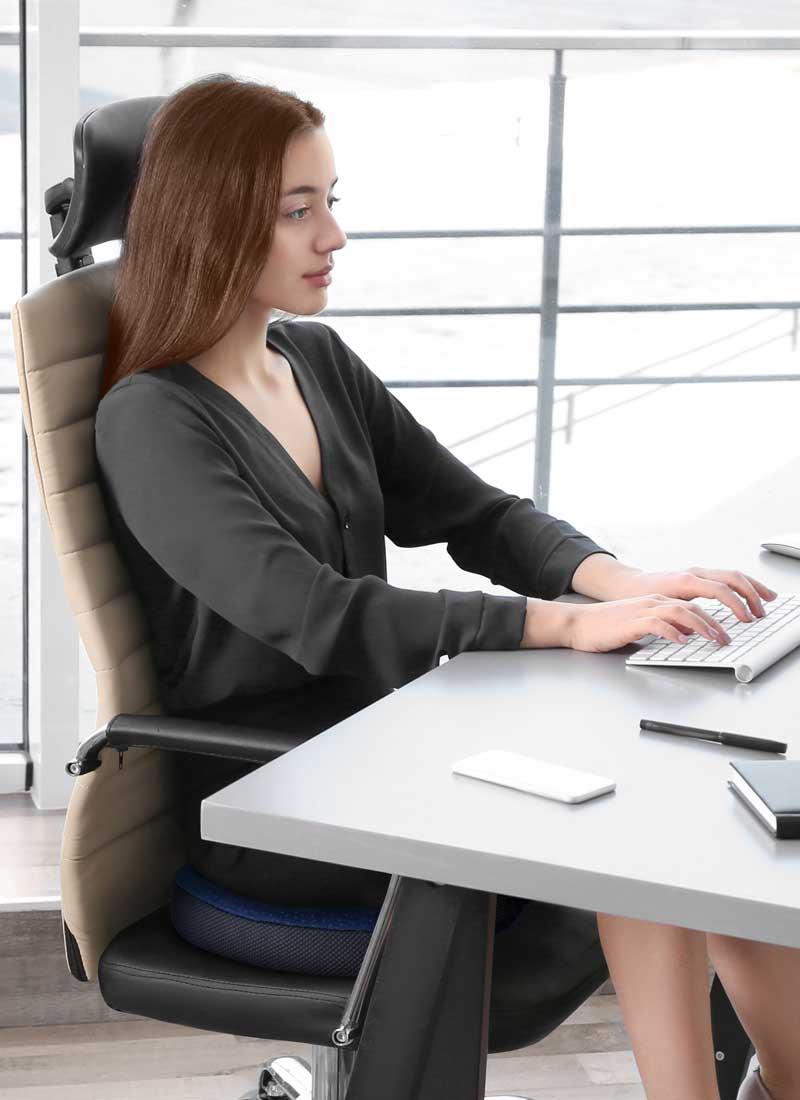Dieses Bild veranschaulicht eine junge Frau am Bürotisch, sitzend auf casimum® Bürostuhl Sitzkissen